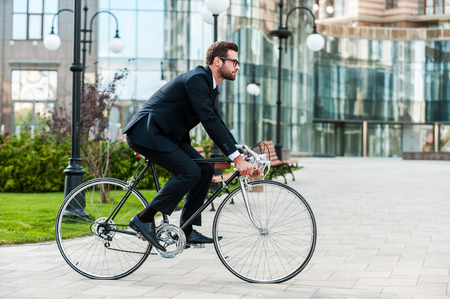 acion: El ir a todas partes en su bicicleta. Vista lateral del hombre de negocios joven mirando hacia adelante, mientras viajaba en su bicicleta