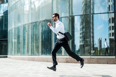 corriendo: Corriendo a trabajar. Longitud total de joven empresario mirando hacia adelante mientras se ejecuta a lo largo de la calle