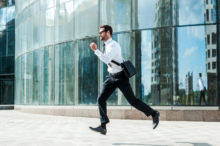 man side view: Hurrying to work. Full length of young businessman looking forward while running along the street