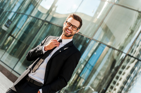office buildings: Successful businessman. Smiling young businessman adjusting his necktie and looking at camera while standing outdoors with office building in the background
