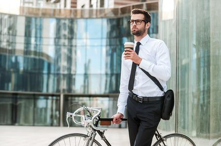 empleado de oficina: Tomarse el tiempo para disfrutar de esta ma�ana. joven hombre de negocios pensativo que sostiene la taza de caf� y mirando a otro lado mientras se apoya en su bicicleta con el edificio de oficinas en el fondo Foto de archivo