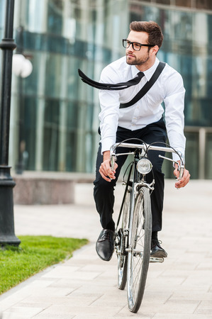 Hurrying to office. Full length of handsome young businessman looking away while riding on his bicycle