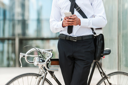 man style: Staying in touch. Close-up of young businessman holding mobile phone while leaning at his bicycle with office building in the background