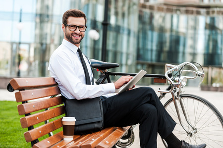 staying: Staying ahead with new technologies. Side view of smiling young businessman holding digital tablet and looking at camera while sitting on the bench near his bicycle Stock Photo