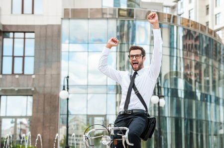 expressing positivity: It was successful day! Low angle view of cheerful young businessman keeping arms raised and expressing positivity while riding on his bicycle