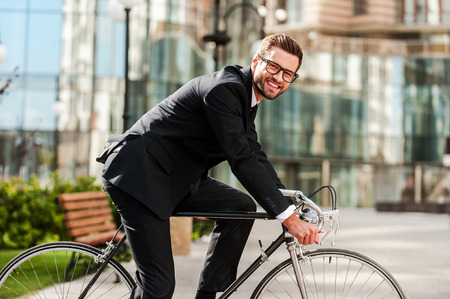 自転車通勤のための完璧な一日。陽気な青年実業家カメラ目線と彼の自転車に乗りながら笑顔の側面図