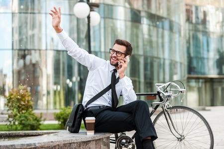 personas saludando: ¡Estoy aquí! Hombre de negocios joven alegre que habla en el teléfono móvil y saludando a alguien mientras está sentado cerca de su bicicleta con edificio de oficinas en el fondo