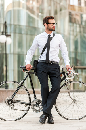 preferred: Preferred mode of transport. Full length of handsome young businessman leaning at his bicycle and looking away while standing outdoors