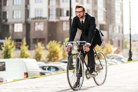 empresario: El ciclismo es el camino hacia el progreso! Longitud total de joven apuesto hombre de negocios mirando hacia adelante, mientras viajaba en su bicicleta Foto de archivo