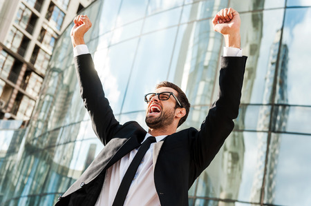 expressing positivity: On the top of business world. Low angle view of excited young businessman keeping arms raised and expressing positivity while standing outdoors with office building in the background Stock Photo