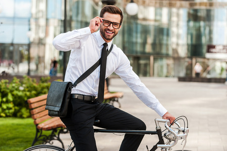 To work on wheels. Side view of smiling young businessman looking at camera and adjusting eyewear while riding on his bicycle