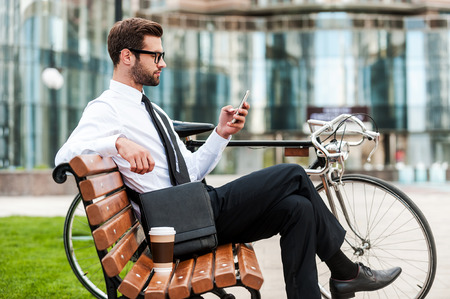 office phone: Young and successful. Side view of handsome young businessman holding mobile phone while sitting on the bench near his bicycle with office building in the background Stock Photo