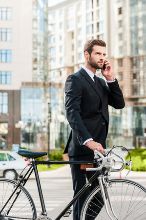 businessman phone: I will be in a minute. Confident young businessman rolling his bicycle and talking on the mobile phone while walking outdoors