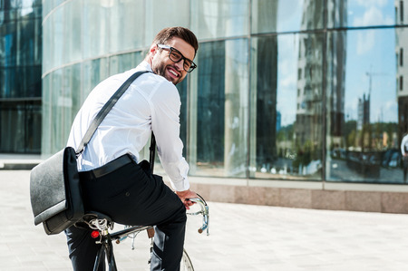 Green way to get to office. Rear view of joyful young businessman looking at camera and smiling while riding on his bicycle with office building in the background