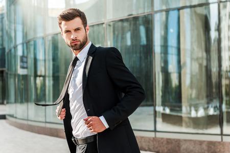 modelos hombres: Líder de negocios. Hombre de negocios joven confidente que ajusta su chaqueta y mirando a la cámara mientras está de pie al aire libre con edificio de oficinas en el fondo