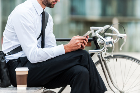 cycling: Sending business message. Cropped image of young businessman holding mobile phone while sitting near his bicycle outdoors