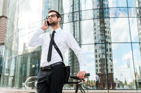 businessman phone: Catching up on the way to work. Low angle view of handsome young businessman talking on the mobile phone while leaning at the bicycle Stock Photo