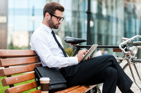 man outdoors: Checking his business schedule. Side view of confident young businessman working on digital tablet while sitting on the bench near his bicycle with office building in the background