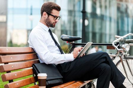 exteriores: Comprobación de su agenda de negocios. Vista lateral del hombre de negocios joven confidente que trabaja en la tablilla digital mientras se está sentado en el banquillo junto a su bicicleta con edificio de oficinas en el fondo