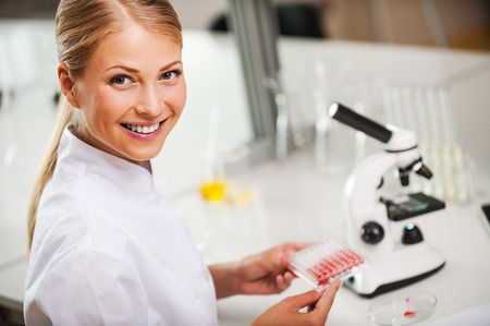 researches: Confident at her researches. Top view of happy female scientist in white uniform holding microtiter plate and looking at camera while sitting at her working place