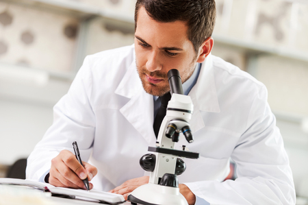 white coat: Committed to find the cure. Handsome young scientist in white uniform using microscope and writing in note pad while sitting at his working place