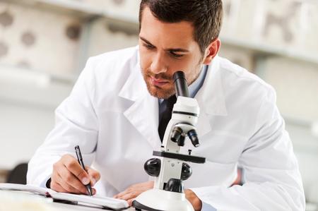 persona escribiendo: Comprometidos para encontrar la cura. Joven científico hermoso en el uniforme blanco que usa el microscopio y la escritura en el bloc de notas mientras está sentado en su lugar de trabajo Foto de archivo