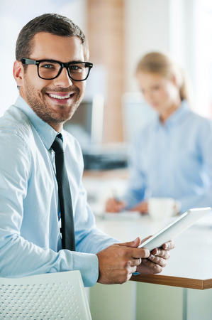 Confident business experts. Cheerful young businessman in formalwear holding digital tablet and looking at camera while his female colleague working in the background Stock Photo - 44278201