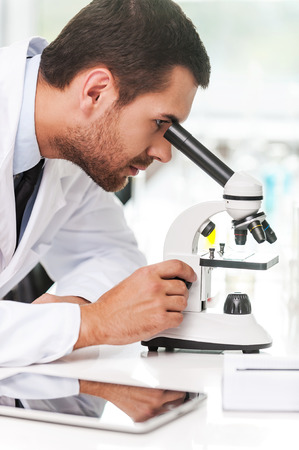 place of research: Research and development. Side view of concentrated young scientist in white uniform using microscope while sitting at his working place