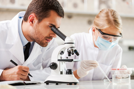 Improving modern medicine. Two young scientists making experiments while sitting in the laboratory 스톡 콘텐츠