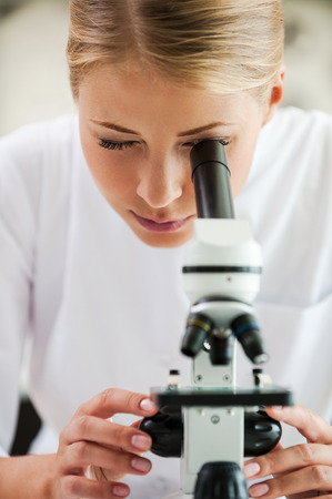 closer: Taking closer look. Concentrated young female scientist using microscope while working in the laboratory Stock Photo