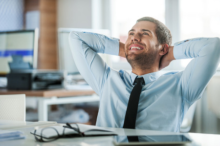 job satisfaction: Job satisfaction. Cheerful businessman in formalwear holding head in hands while sitting at his desk in the office
