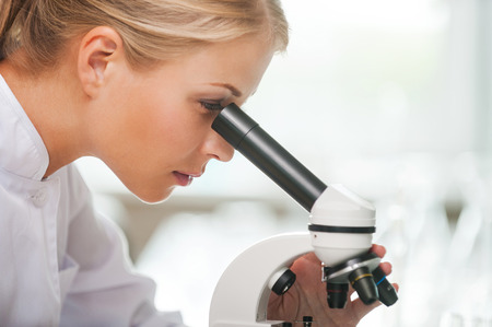 closer: Taking closer look at bacteria. Side view of concentrated young female scientist using microscope while working in the laboratory Stock Photo