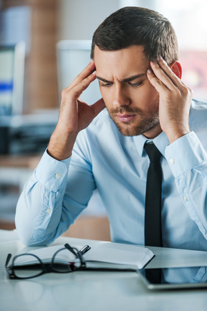 hard day at the office: Hard day in office. Frustrated businessman touching his head while sitting at his working place Stock Photo