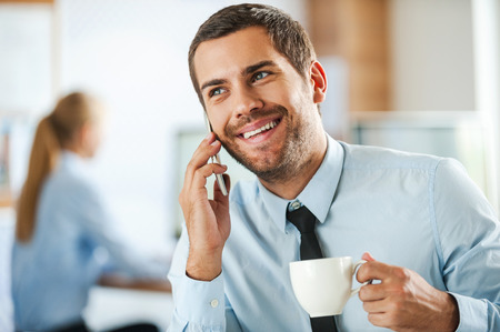good: Always in good mood. Cheerful young businessman in formalwear talking on the mobile phone and holding cup of coffee while his female colleague working in the background