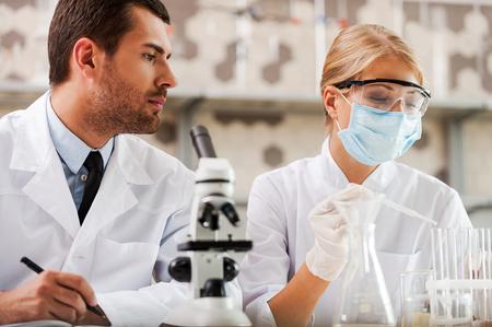 experimento: Investigaciones en el laboratorio de ciencias. ángulo de visión baja de dos jóvenes científicos realizar experimentos mientras está sentado en el laboratorio