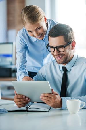 새로운 비즈니스 프로젝트에 대해 토론하기. 함께 웃고 디지털 태블릿을 바라 보는 formalwear의 두 행복 젊은이들 스톡 콘텐츠 - 44278164