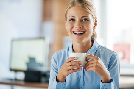 drink coffee: Taking coffee break. Cheerful young businesswoman in formalwear holding cup of coffee and looking at camera while sitting at her working place
