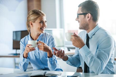 empleado de oficina: Compartiendo noticias frescas. Dos jóvenes alegres en ropa formal sosteniendo tazas de café y hablando de algo mientras trabajan juntos