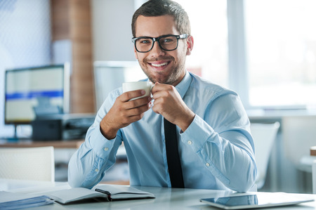 only man: Coffee break. Cheerful young businessman in formalwear holding cup of coffeeand looking at camera while sitting at his working place