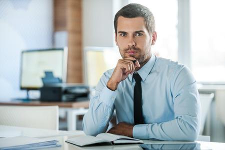 La cara del liderazgo plenaria. Hombre de negocios pensativo en ropa formal de la mano en la barbilla mientras se está sentado en su lugar de trabajo Foto de archivo