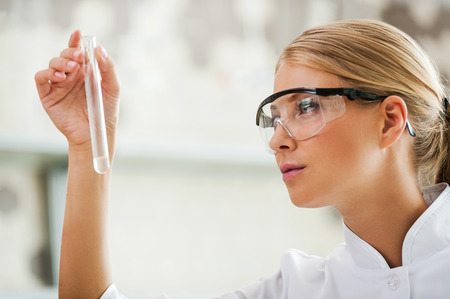 laboratory coat: Passionate about her work. Side view of young female scientist holding test tube and looking at it while working in the laboratory Stock Photo