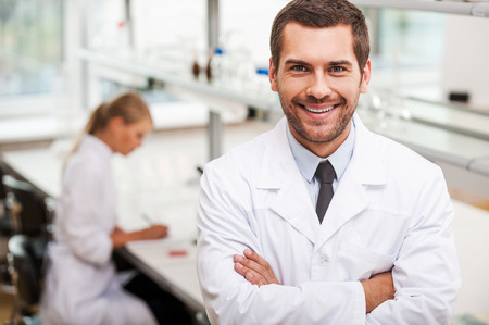 young man smiling: Confident scientist. Happy young male scientist keeping arms crossed and looking at camera while his female colleague working in the background Stock Photo