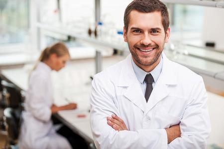 Zelfverzekerd wetenschapper. Gelukkig jonge mannelijke wetenschapper houden gekruiste armen en kijken naar de camera terwijl zijn vrouwelijke collega het werken op de achtergrond
