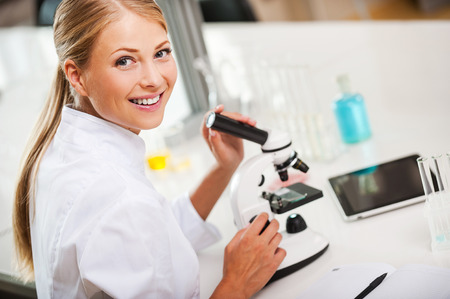 medical professional: Lovely day in the laboratory. Top view of smiling young female scientist using microscope and looking at camera while working in the laboratory