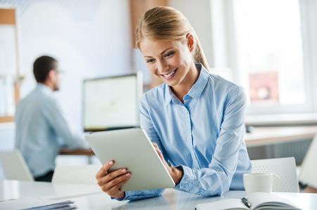 empleado de oficina: El éxito de negocios en el trabajo. Joyful joven empresaria en ropa formal trabaja en la tablilla digital y sonriendo mientras se trabaja en la oficina