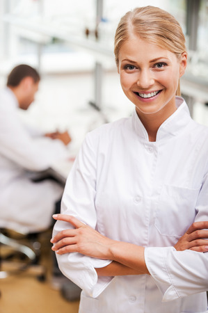 white coat: Cheerful scientist. Beautiful young female scientist keeping arms crossed and looking at camera while her male colleague working in the background Stock Photo