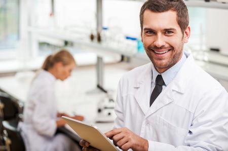 bata blanca: Documentar el resultado de los experimentos. Sonriendo joven científico masculino que sostiene la tableta digital y mirando a la cámara mientras su colega de trabajo en segundo plano