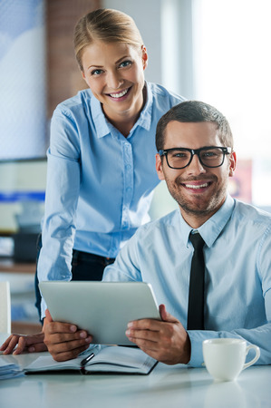 Confident business experts. Two cheerful young people in formalwear smiling and looking at camera while working together