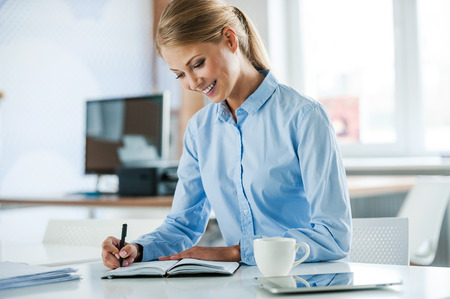 formalwear: Working with pleasure. Beautiful young businesswoman in formalwear writing in note pad while sitting at her working place