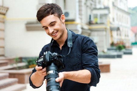only man: Finding the right shoot. Happy young man holding camera and smiling while standing outdoors Stock Photo